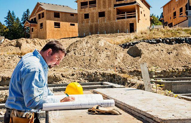 Строитель делает пометки в плане строительства