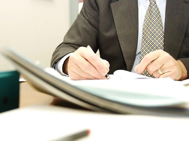 Мужчина заполняет документы